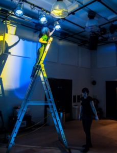 Image of a young girl up a ladder working with theatre lights
