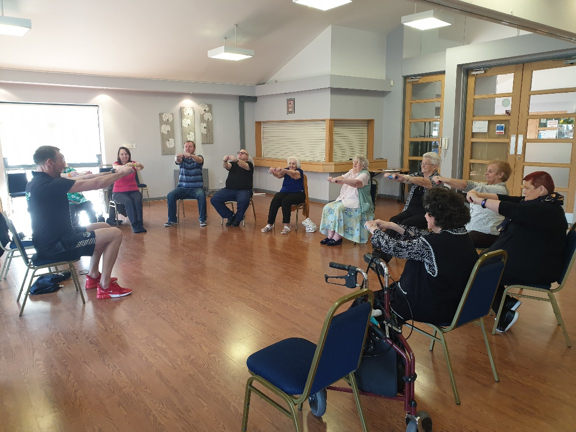 People sitting in a circle doing chair based exercise