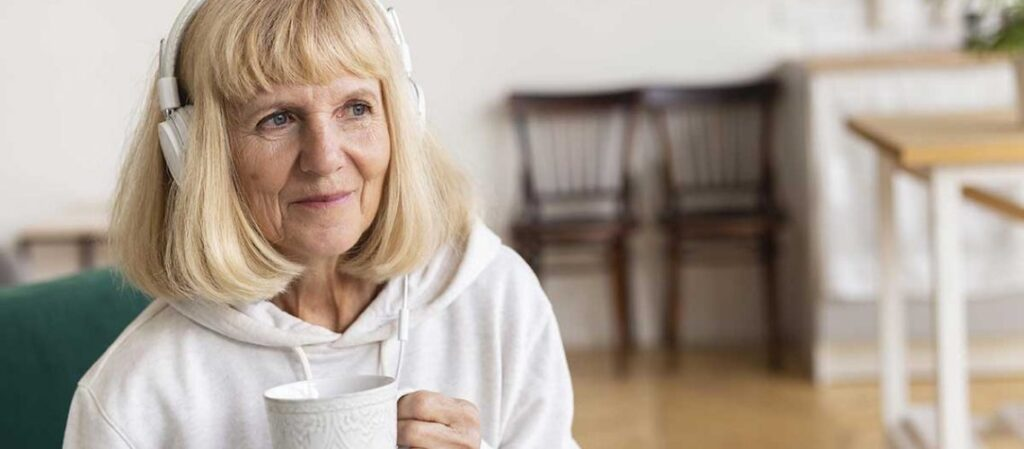 Older lady wears headphones and holds a coffee mug